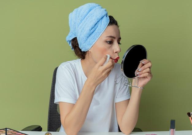Młoda ładna dziewczyna siedzi przy stole do makijażu z narzędziami do makijażu i ręcznikiem na głowie, trzymając się i patrząc w lustro i wycierając szminkę serwetką na białym tle na oliwkowym tle