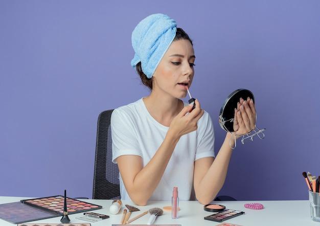 Młoda ładna dziewczyna siedzi przy stole do makijażu z narzędziami do makijażu iz ręcznikiem na głowie, trzymając i patrząc w lustro oraz nakładając błyszczyk na białym tle na fioletowym tle