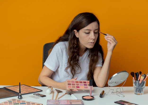 Młoda ładna dziewczyna siedzi przy stole do makijażu z narzędziami do makijażu, patrząc w lustro i stosując cień do powiek na białym tle na pomarańczowym tle