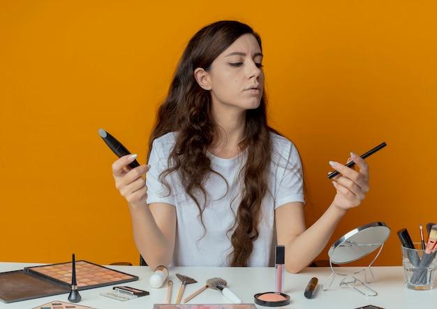 Młoda ładna dziewczyna siedzi przy stole do makijażu z narzędziami do makijażu, trzymając i patrząc na eyeliner i tusz do rzęs
