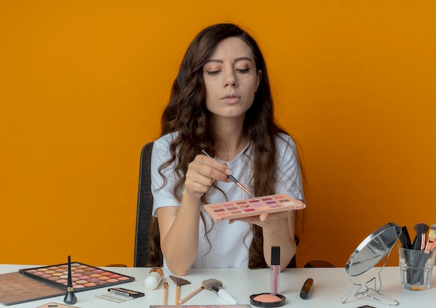 Młoda ładna dziewczyna siedzi przy stole do makijażu z narzędziami do makijażu, trzymając i patrząc na paletę cieni do powiek i trzymając pędzel do cieni do powiek na białym tle na pomarańczowym tle