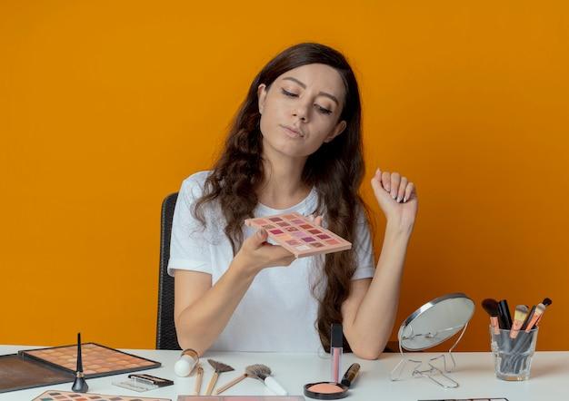 Młoda ładna dziewczyna siedzi przy stole do makijażu z narzędziami do makijażu, trzymając i patrząc na paletę cieni do powiek jedną ręką w powietrzu na białym tle na pomarańczowym tle