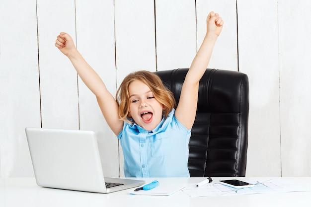 Młoda ładna dziewczyna siedzi w miejscu pracy, radując się w biurze.