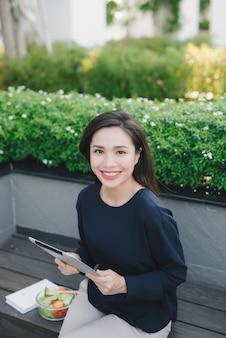 Młoda ładna dziewczyna siedzi w parku, pracując, przewijając tablet