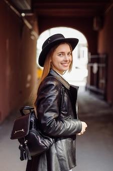 Młoda ładna dziewczyna spaceruje po mieście uśmiechając się i pozując