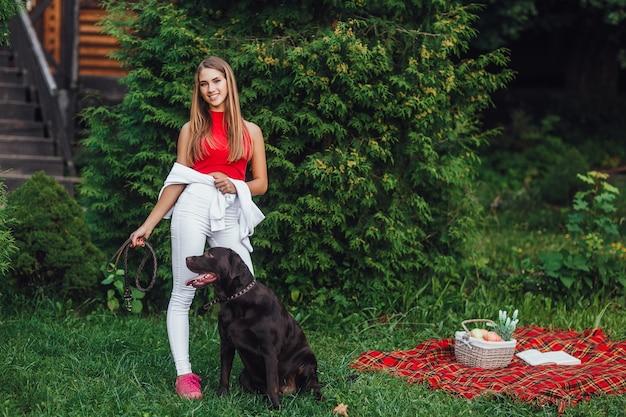 Młoda ładna dziewczyna spaceruje po parku ze swoim labradorem, bawią się razem