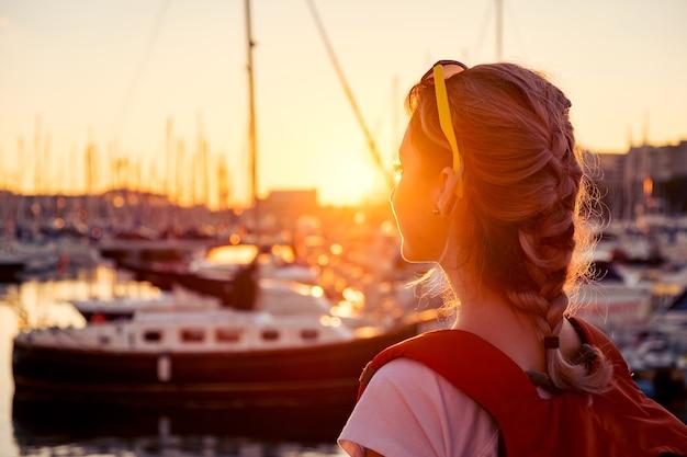 Młoda ładna dziewczyna stoi na molo i patrzy na zatokę z jachtami o zachodzie słońca