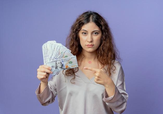 Młoda ładna dziewczyna trzyma i wskazuje na gotówkę