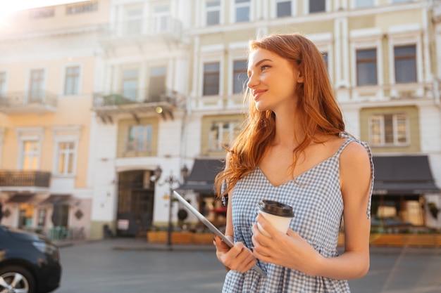 Młoda ładna dziewczyna trzyma komputer osobisty pastylkę i filiżankę kawy