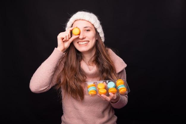 Młoda ładna dziewczyna trzyma pudełko z makaronikami na czarnym tle uśmiecha się do kamery.