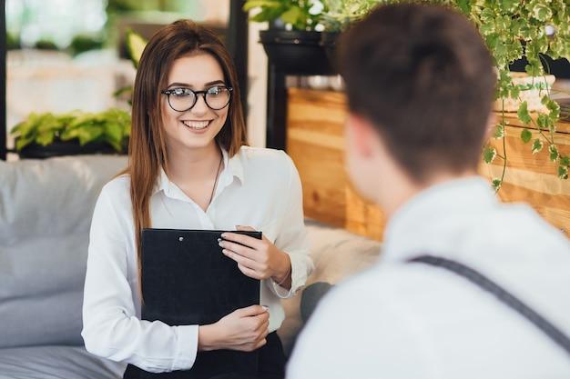 Młoda ładna dziewczyna w białej koszuli w okularach z folderu. na pierwszym planie mężczyzna jest zamazany