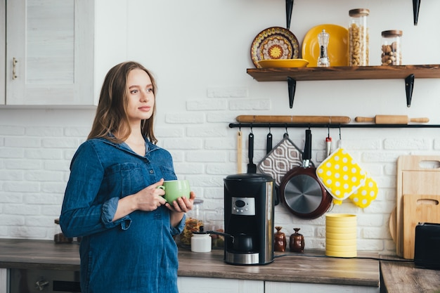 Młoda ładna dziewczyna w ciąży pracuje w domu w trybie samoizolacji w kwarantannie i odpoczywa przy kawie