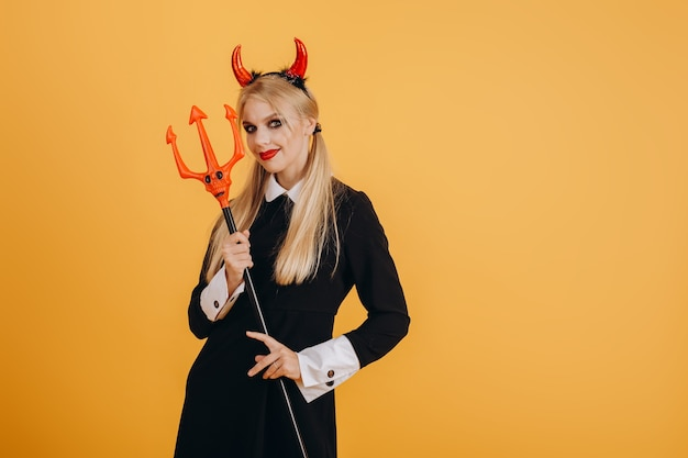 Młoda, ładna dziewczyna w kostiumie na halloween z rogami diabła na głowie i widłami w dłoniach