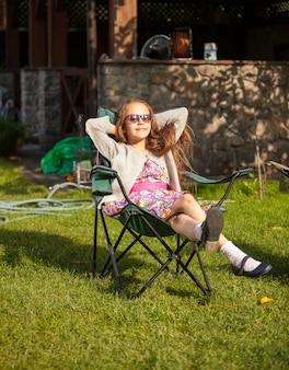 Młoda ładna dziewczyna w okularach przeciwsłonecznych, opalając się na podwórku