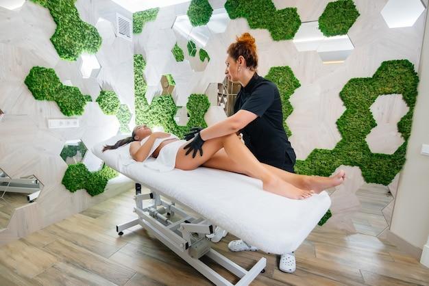 Młoda ładna dziewczyna w spa wykonuje profesjonalny masaż kosmetyczny. pielęgnacja ciała. salon piękności.