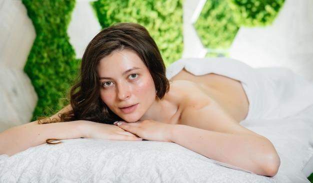 Młoda ładna dziewczyna w spa wykonuje profesjonalny masaż kosmetyczny