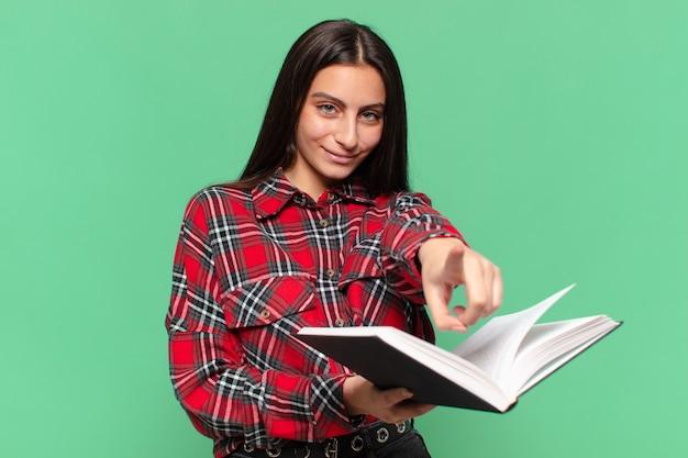 Młoda ładna dziewczyna wskazując gest. koncepcja studenta