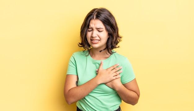 Młoda ładna dziewczyna wygląda na smutną, zranioną i załamaną, trzymając obie ręce blisko serca, płacząc i czując się przygnębiona