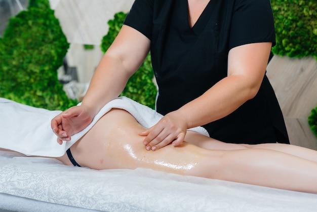 Młoda ładna dziewczyna wykonuje profesjonalny masaż miodem w spa. pielęgnacja ciała. salon piękności.