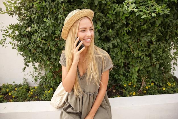 Młoda ładna dziewczyna z długimi blond włosami pozuje nad zielonymi krzakami, ubrana w romantyczną sukienkę i kapelusz, trzymając telefon w dłoni i patrząc na bok z radością