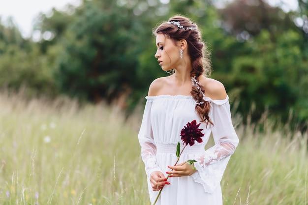 Młoda ładna dziewczyna z kwiatem w lekkim opatrunkowym spacerze przy gazonem blisko lato lasu