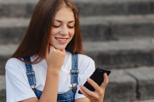 Młoda ładna dziewczyna z teczki obsiadanie na schodkach i writing sms na telefonie