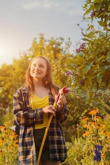Młoda ładna dziewczyna zabawy w ogrodzie podlewania roślin z wężem. uśmiechając się podczas ulubionego hobby.