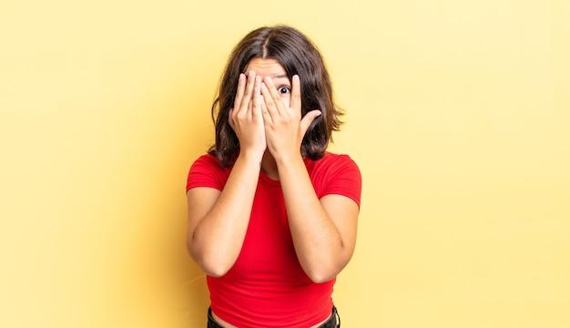 Młoda ładna dziewczyna zakrywa twarz rękami, zerka między palcami ze zdziwionym wyrazem twarzy i patrzy w bok