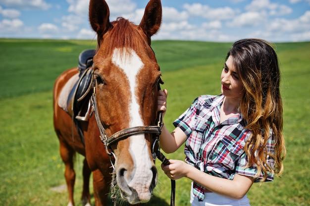 Młoda ładna dziewczyna zostaje z koniem na polu przy słonecznym dniem.