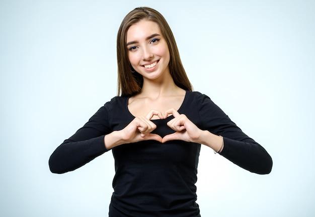 Młoda ładna dziewczyna zrobić serce rękami