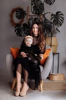 Młoda ładna elegancka matka z małą śliczną córką ściska i siedzi na krześle w domu w ciemnych sukniach, szczęśliwa uśmiechnięta rodzina, stylu życia pojęcia ludzie. dzień matki, dziecka