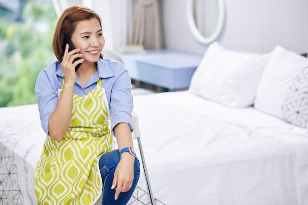 Młoda, ładna gospodyni azjatycka rozmawia przez telefon z przyjacielem po sprzątaniu mieszkania