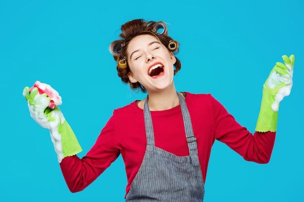 Młoda ładna gospodyni śpiewa piosenki podczas mycia okien w rękawiczkach