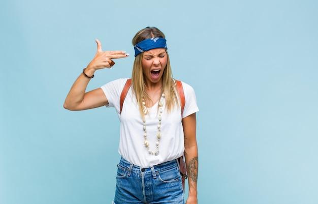 Młoda ładna hipis kobieta szuka nieszczęśliwego i zestresowanego, samobójczy gest czyniąc znak pistoletu ręką, wskazując na głowę
