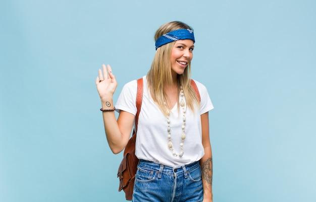 Młoda ładna hipis kobieta uśmiecha się radośnie i wesoło, macha ręką, wita i wita lub żegna się