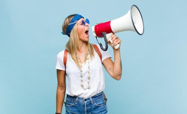 Młoda ładna hipis kobieta ze skórzaną torbą i megafonem