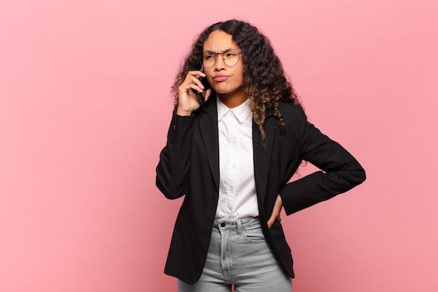 Młoda ładna hiszpańska kobieta biznesowa i koncepcja smartfona