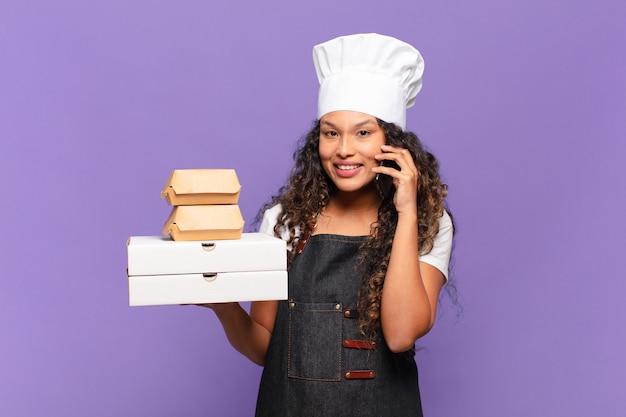 Młoda ładna hiszpańska kobieta kucharz obsługuje zamówienia na koncepcji telefonu