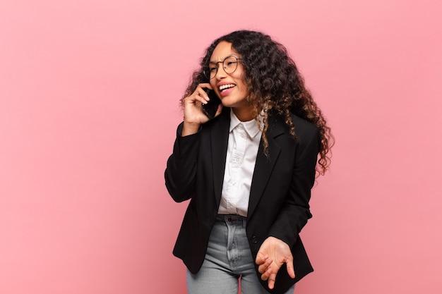 Młoda ładna hiszpańska kobieta szczęśliwa i zaskoczona koncepcja biznesowa i smartfonowa ekspresji
