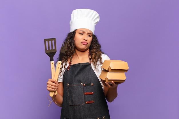 Młoda ładna Hiszpańska Kobieta Zdezorientowana Koncepcja Grilla Szefa Kuchni Premium Zdjęcia