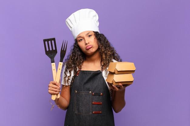 Młoda ładna hiszpańska kobieta zdezorientowana koncepcja grilla szefa kuchni