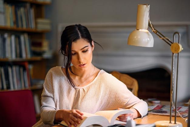 Młoda ładna i entuzjastyczna studencka dziewczyna czyta książkę w bibliotece uniwersyteckiej pod lampą stołową