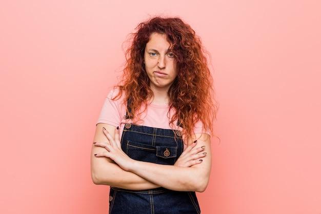 Młoda ładna imbirowa rudzielec kobieta jest ubranym cajgu dungaree nieszczęśliwego patrzejący w kamerze z sarkastycznym wyrażeniem.