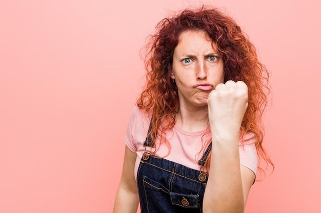 Młoda ładna imbirowa rudzielec kobieta jest ubranym dżinsy drelich pokazywać agresywny wyraz twarzy.