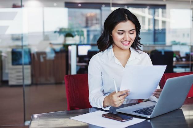 Młoda ładna indyjska kobieta trzyma dokument i siedzi