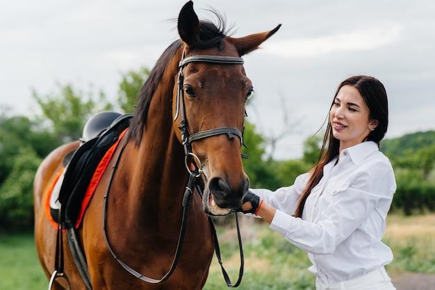 Młoda ładna jeźdźca pozuje na ranczo w pobliżu pełnej krwi ogiera. jazda konna, wyścigi konne.