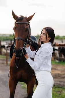 Młoda, ładna jeźdźca pozuje na ranczo w pobliżu pełnej krwi ogiera.