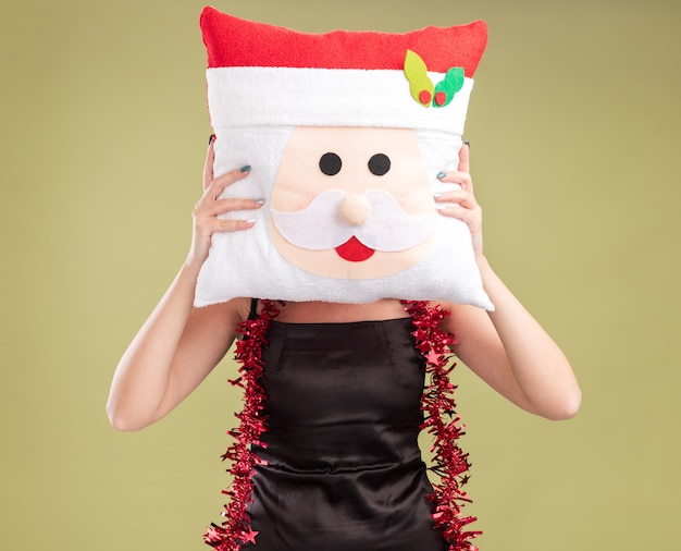 Młoda ładna kaukaska dziewczyna nosi świąteczny wieniec i blichtr girland wokół szyi, trzymając poduszkę świętego mikołaja przed twarzą na białym tle na oliwkowo-zielonym tle