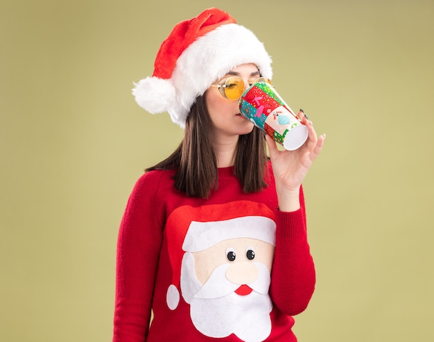 Młoda ładna kaukaska dziewczyna ubrana w sweter świętego mikołaja i kapelusz w okularach pijąca kawę z plastikowego kubka świątecznego na białym tle na oliwkowo-zielonym tle