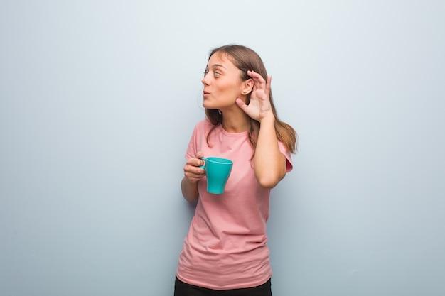 Młoda ładna kaukaska kobieta próbuje słuchać plotek. trzyma kubek.